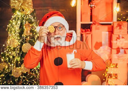Santa Claus Enjoys Cookies And Milk Left Out For Him On Christmas Eve. Milk And Gingerbread Cookie F