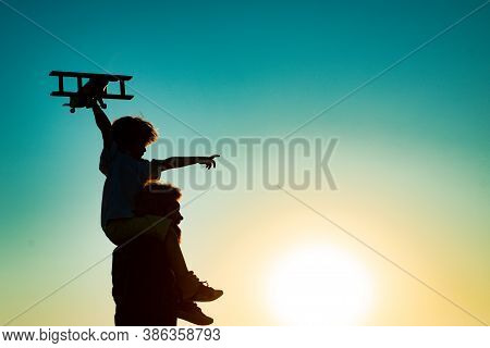Sunset Silhouette Of Father Carrying His Son On Shoulders. Child Son Pilot And Dad Daddy Father With
