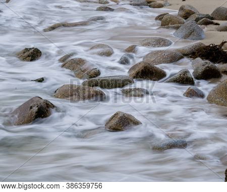 Waves Breaking On A Rocky Stoney Shoreline In Pacific, Coastal Town Of Monterey (pacific Grove). Cal