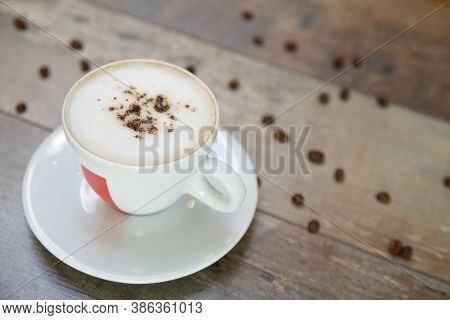 Cup Of Cappuccino And Beans On A Wooden Table