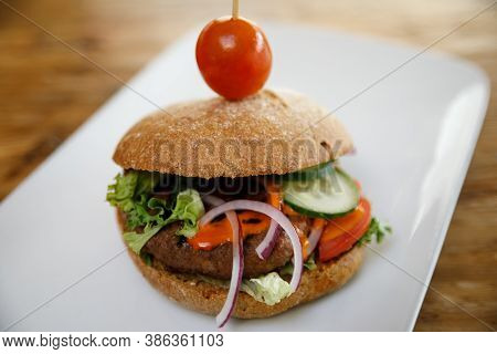 A Burger Isolated On A White Plate With Negative Space.