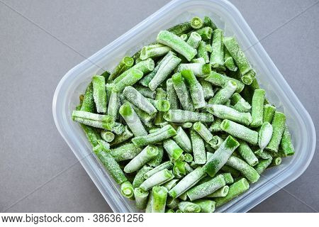 Frozen Green Beans In A Plastic Container For Long-term Storage. Deep Freezing Of Vegetables. Frozen