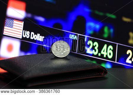 A Quarter Of Us Dollar Coins On Obverse (usd) On Black Wallet On Black Floor With Digital Board Of C