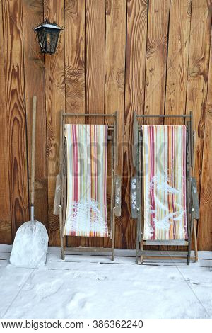 Deckchairs Folded And Placed Against A Wooden Wall On A Terrace Covered With Snow