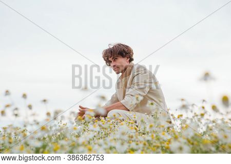 Tall Handsome Man Sitting On A Back Of A Chair In Camomile Flowers Field