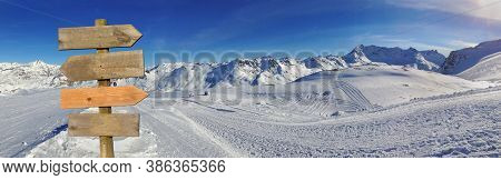 Wooden Sign In Front Of A Beautiful Snowy Mountain Landscape In Winter Under Blue Sky