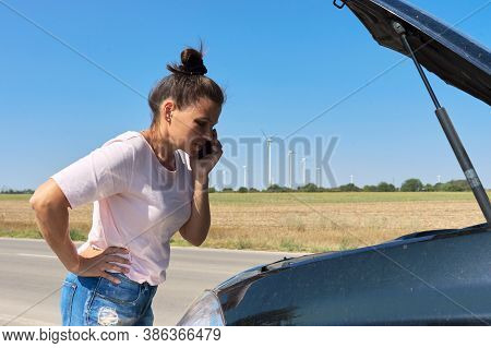 Car Breakdown, Unhappy Woman On The Road With Open Car Hood Talking On The Mobile Phone. Car Repair