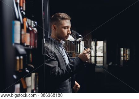Sommelier Man Holds Glass With Red Wine Tests Aroma And Color