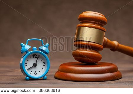 Alarm Clock And Hammer Judge Gavel On Brown