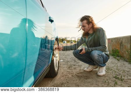 Young Caucasian Man Checking Air Pressure Of Car Tire On Local Road Side While Traveling, Male Drive