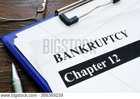 Papers About Bankruptcy Chapter 12 And Pen On The Desk.