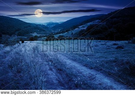Country Road Through Rural Field At Night. Suburban Summer Landscape In Mountains In Full Moon Light