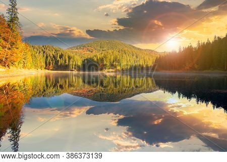 Mountain Lake Among The Forest At Sunset. Trees In Colorful Foliage. Beautiful Landscape In Autumn E