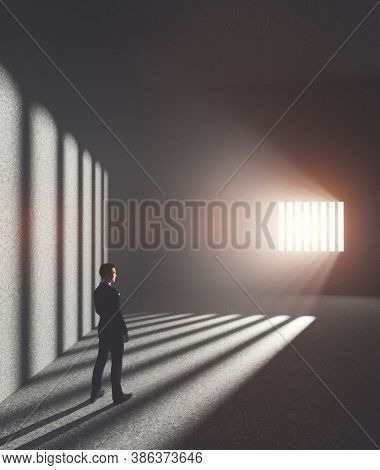 Businessman in jail looking at light coming from behind prison bars. Concept of economic offence, punishment but also hope of freedom. 3D illustration