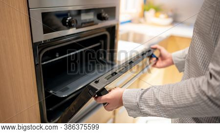 Male Hand Opening Oven Door In The Kitchen Showroom. Buying Cooking Appliance For Domestic Kitchen.