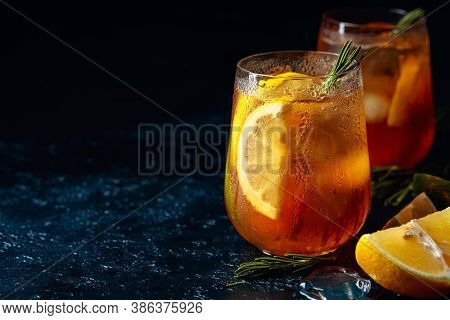 Traditional Iced Tea With Lemon, Lime And Ice Garnished With Rosemary Twigs. Frozen Glasses With Cit
