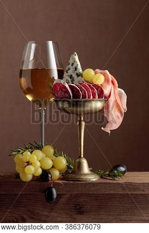 Glass Of Wine With Snacks On A Brown Background. Wine, Blue Cheese, Dry-cured Sausage, Prosciutto, G