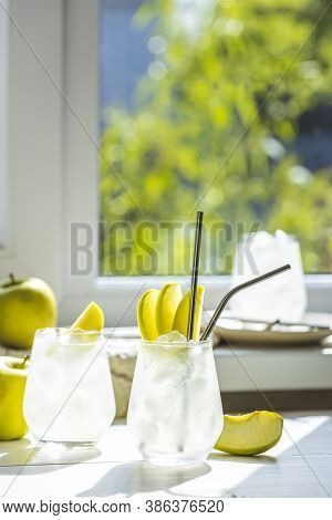 Summer Cocktail With Green Apple And Ice On The White Table Near Window In The Sunny Summertime. Sel