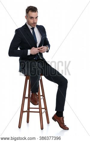Confident businessman fixing his jacket while sitting on a stool on white studio background