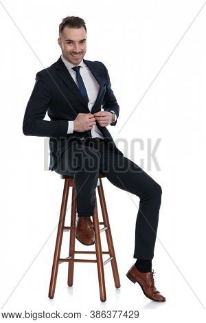 Positive businessman laughing and adjusting his jacket while sitting on a stool on white studio background