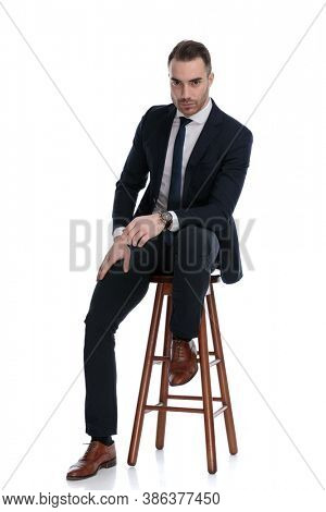 Tough businessman leaning on his leg while sitting on a stool on white studio background