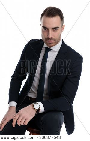 Serious businessman leaning on his leg and looking forward while sitting on a stool on white studio background