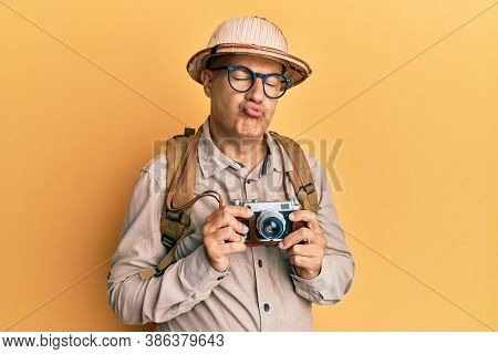 Middle age bald man wearing explorer hat and vintage camera looking at the camera blowing a kiss being lovely and sexy. love expression.