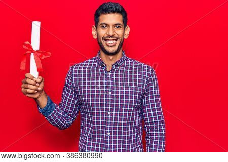 Young latin man holding graduate degree diploma looking positive and happy standing and smiling with a confident smile showing teeth