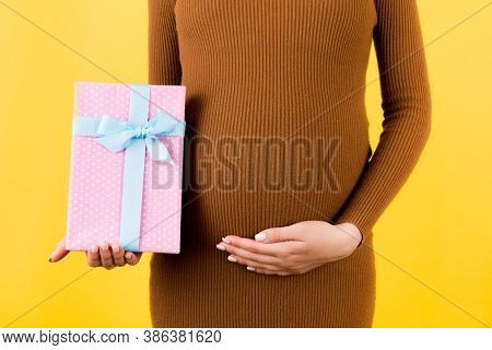 Cropped Image Of Pink Spotted Gift Box In Pregnant Womans Hand Against Her Belly At Yellow Backgroun