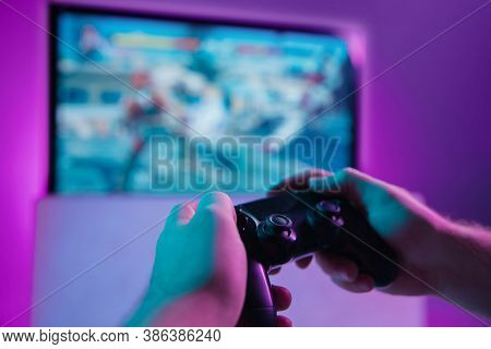 Back View Close Up Of Professional Gamer Playing Online Video Game With His Gameset. Room Lit In Neo