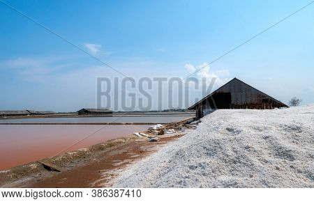 Landscape Of Brine Salt Farm With Blue Sky On Sunny Day. Salt Warehouse. Pile Of Organic Sea Salt. R