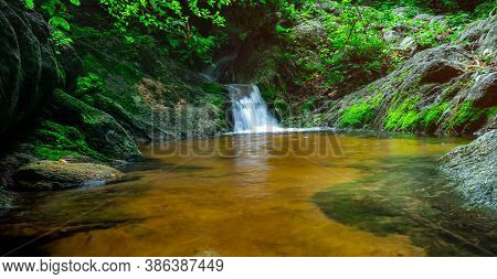 Selective Focus Green Moss On Rock Surface At Small Waterfall In Jungle. Waterfall In Tropical Fores