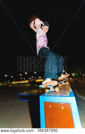 Young Skater Doing Trick Slide On Railing In Skatepark At Night
