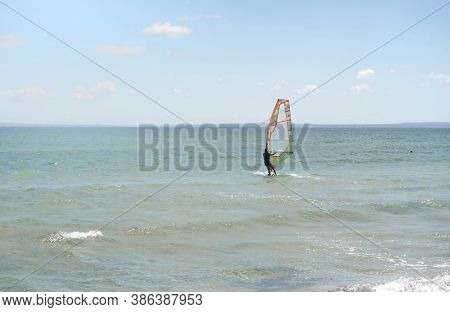 Recreational Water Sports. Windsurfing. Windsurfer Surfing The Wind On Waves In Ocean, Sea. Extreme