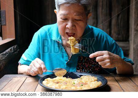 Old Asian Elderly Senior Elder Woman Eating Food At Restaurant. Mature Lifestyle