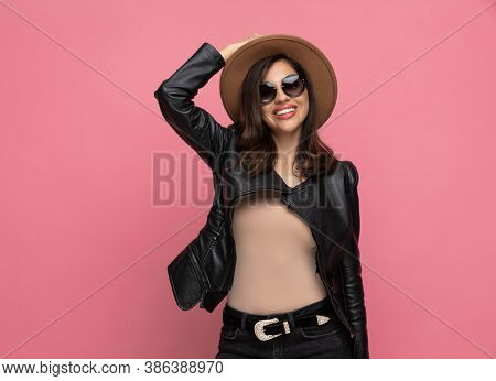 Happy fashion model arranging hat and smiling, wearing sunglasses while standing on pink studio background