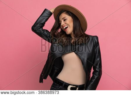 Cheerful fashion model arranging her hat and laughing while standing on pink studio background