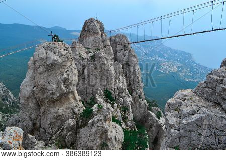 Hanging Suspension Bridge Over An Abyss In Steep Rocks Ai-petri, Crimea. Against The Backdrop Of The