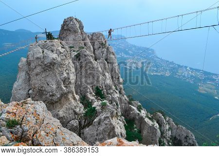 Hanging Suspension Bridge Over An Abyss In Steep Rocks With Going Man. Ai-petri, Crimea. Against The
