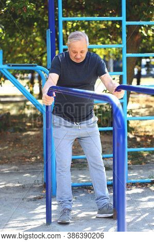 Senior Man Doing Exercises In The Outdoor Gym. The Concept Of Maintaining Health At Any Age. Recover