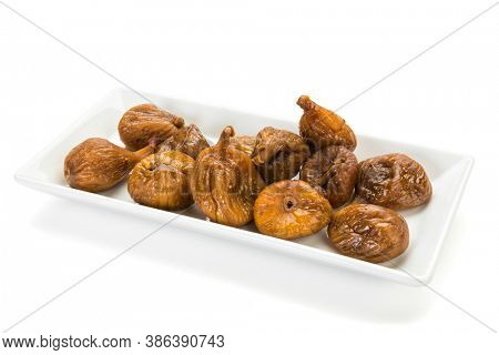Preserved fruit. Dried figs on white platter isolated on white background.