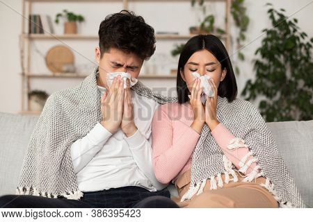 Ill Asian Couple Having Cold, Blowing Nose Sneezing In Paper Tissue Sitting On Couch At Home Feeling
