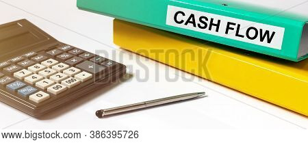 Cash Flow Word Text Inscription On Gren Folder On White Office Table With Calculator, Silver Pen And