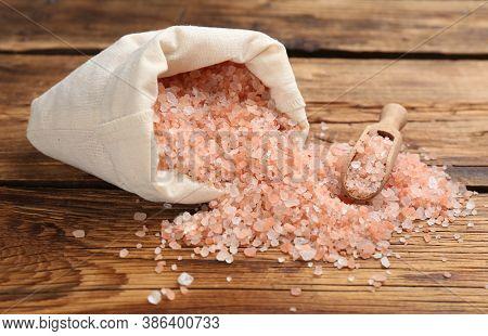 Overturned Sack Of Pink Himalayan Salt On Wooden Table
