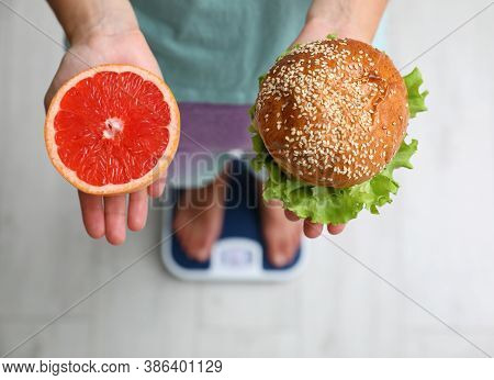 Choice Concept. Top View Of Woman With Grapefruit And Burger Standing On Scales, Closeup