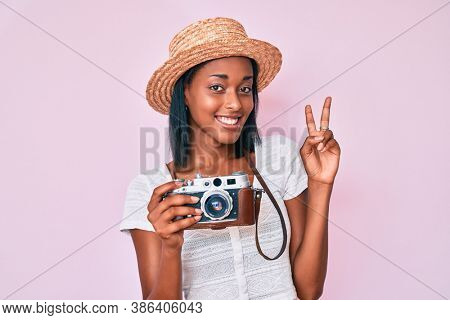 Young african american woman wearing summer hat holding vintage camera smiling looking to the camera showing fingers doing victory sign. number two.