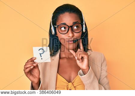 Young african american woman wearing operator headset holding question mark serious face thinking about question with hand on chin, thoughtful about confusing idea