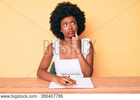 Young african american woman writing book serious face thinking about question with hand on chin, thoughtful about confusing idea