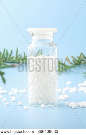 Homeopathic Globules And Glass Bottle Near With Fresh Juniper Branches Close-up On Blue Background.