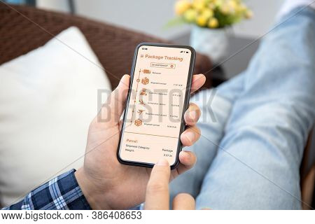 Male Hands Holding Phone With App Tracking Delivery Package On The Screen In The Room House